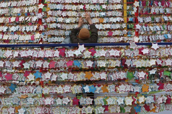 Rows and rows of star-shaped paper wishes line walls in a temple, with one person in the middle of the frame placing another one