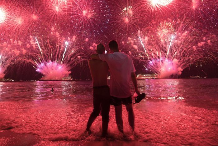 Two men watch the fireworks exploding in bright red over Copacabana Beach.