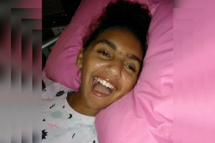 Head and shoulders shot of Denishar Woods laughing with head on pink pillow