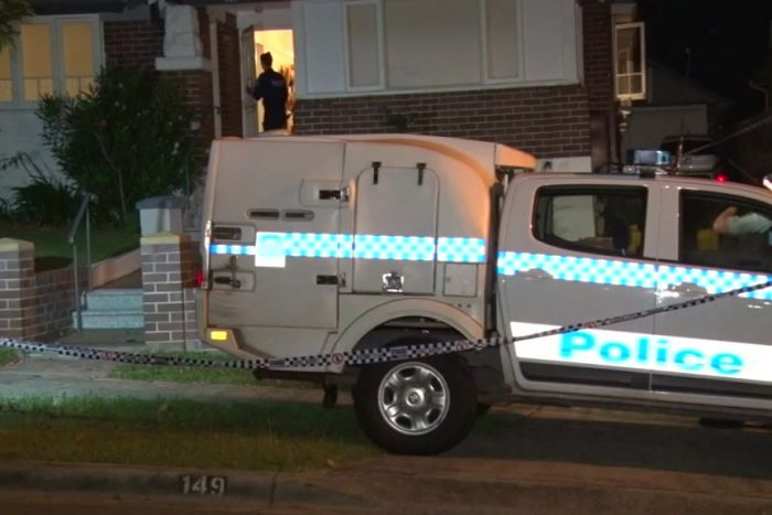 A police car is parked outside a home which is surrounded by police tape.