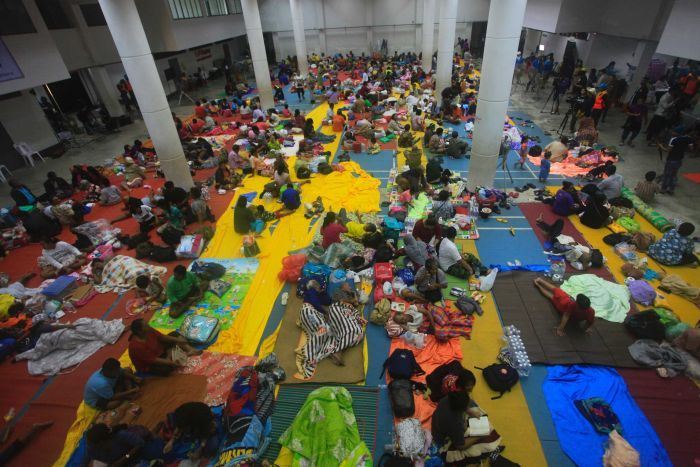 A photo from high up shows an overview of people sitting on the ground with blankets in a hall.