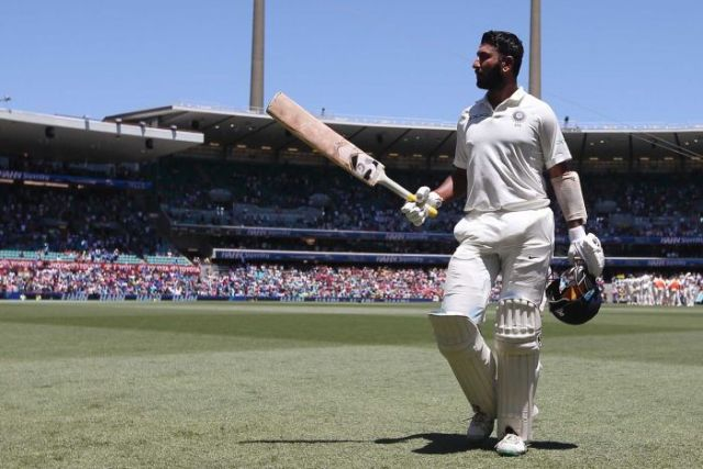 India batsman Cheteshwar Pujara walks across the SCG outfield with his bat raised after getting out in a Test against Australia.