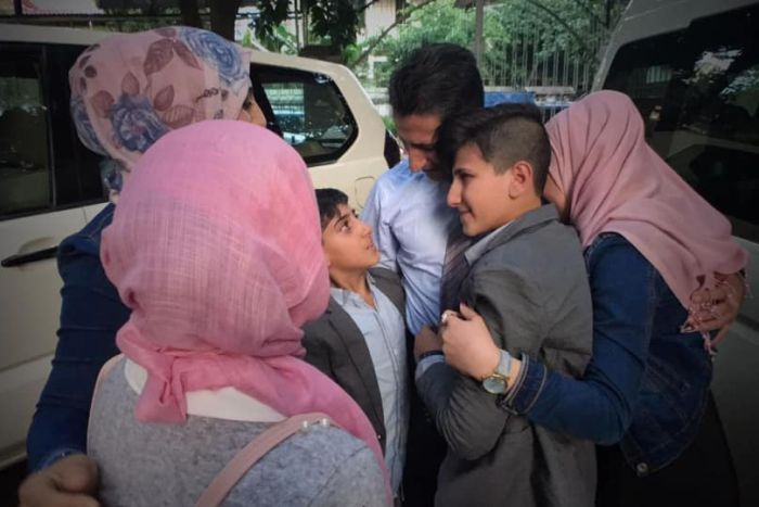 Abdullah Zalghanah embraces his wife and children.