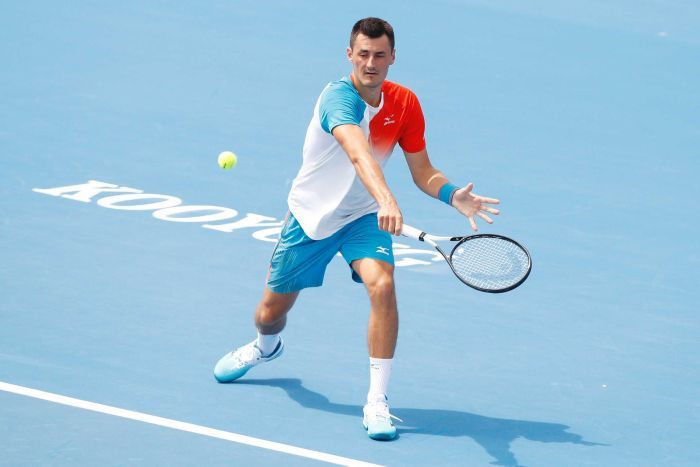 A tennis player hits a back-hand shot with his racquet in his right hand