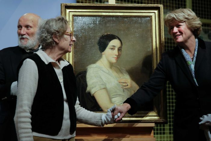 Two women shake hands in front of a painting of a women with black hair.