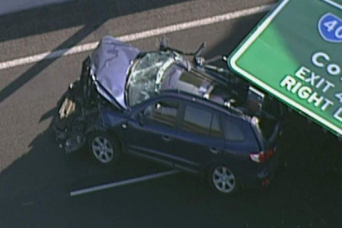 The front of a car is smashed on the Tullamarine Freeway with a road sign lying on the back half of it.