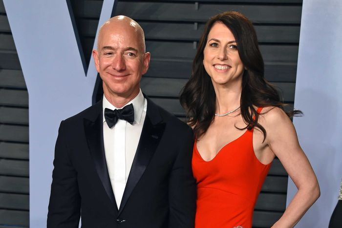 Jeff Bezos wearing a black suit and bow tie, MacKenzie Bezos wears a red evening gown.