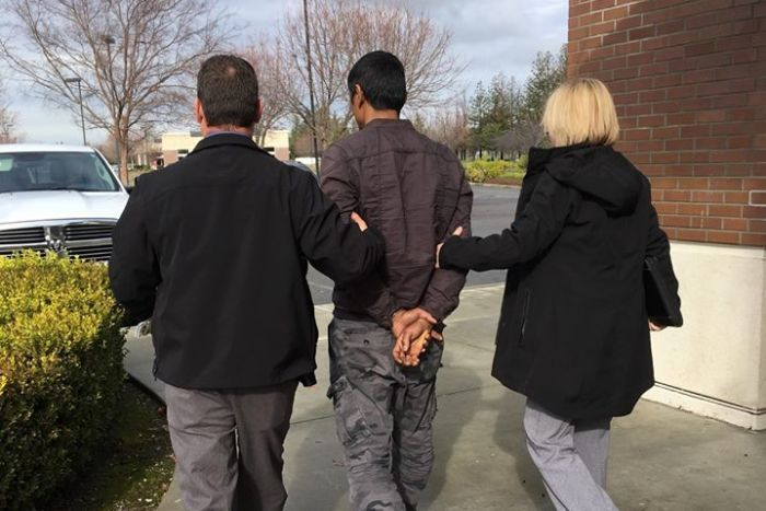 A man in handcuffs pictured from behind being led away by a male and female.