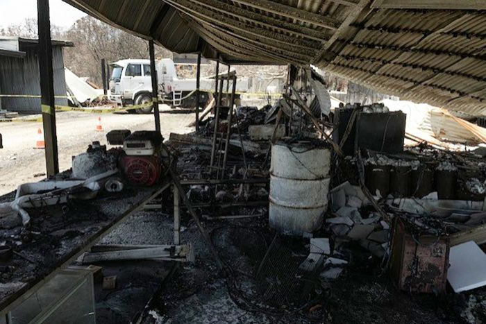 Damaged equipment and shed after a bushfire at apiarist George Spiteri's property at Deepwater.