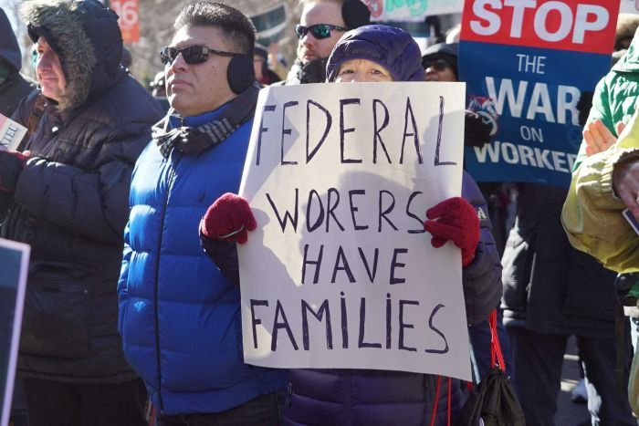 Workers stand in the street protesting with various placards. One woman holds a sign reading: Federal workers have families.