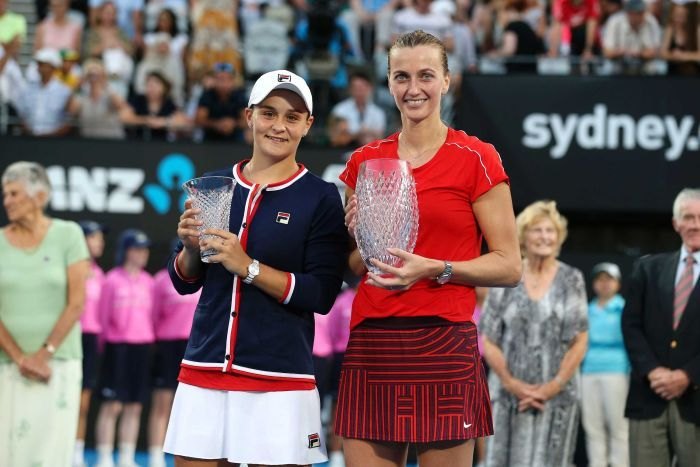 Winner Petra Kvitova and runner-up Ash Barty hold trophies after the Sydney International final.