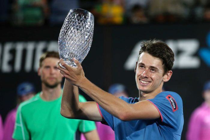 Alex de Minaur grins as he holds a crystal trophy aloft to the left of the frame in both hands while wearing a blue shirt.