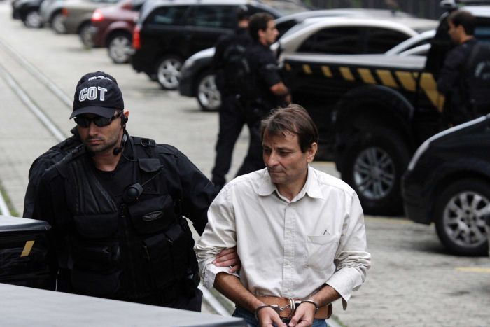 Two federal Brazilian police officers clad in black escort Cesare Battisti, dressed in a white shirt, to a vehicle.