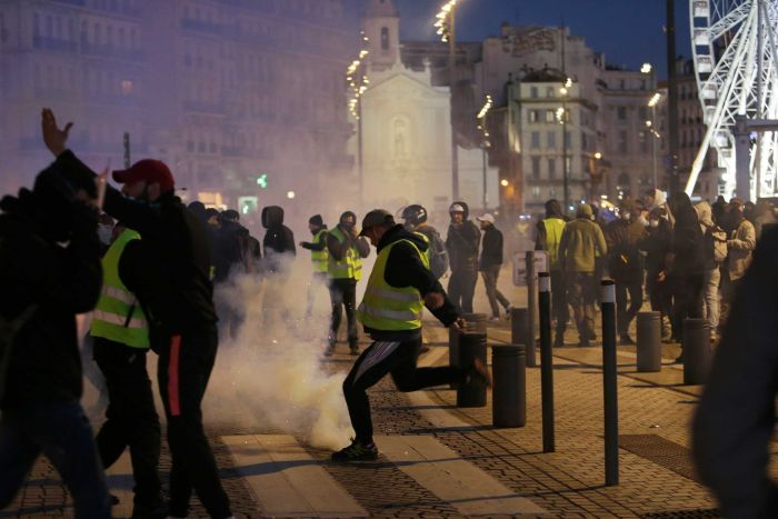 A yellow vest protester kicks a tear gas canister in Marseille within a largely all-male crowd; a Ferris wheel in the distance.