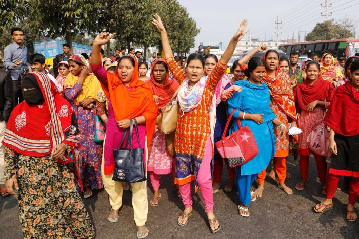 On a Bangladeshi street a large group of women in saris and veils lift their hands and shout in protest.