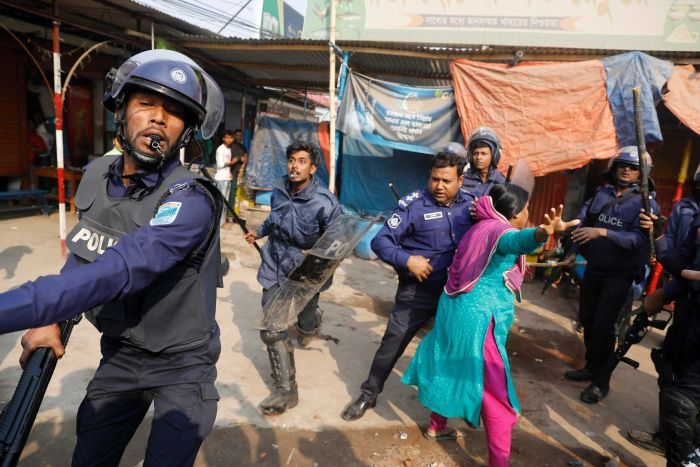 A Bangladeshi woman in a bright blue and purple sari throws her right hand out as six police officers surround her.