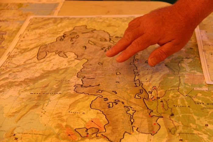 A firefighter points to the Gell River fire on a map