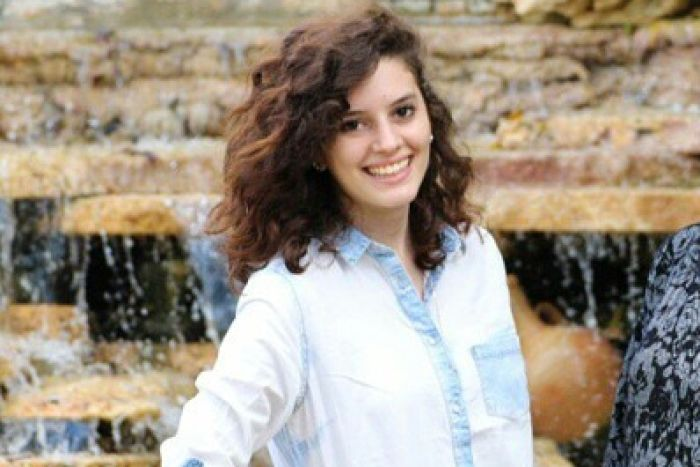 A young woman smiles as she poses for a photograph in front of a fountain.