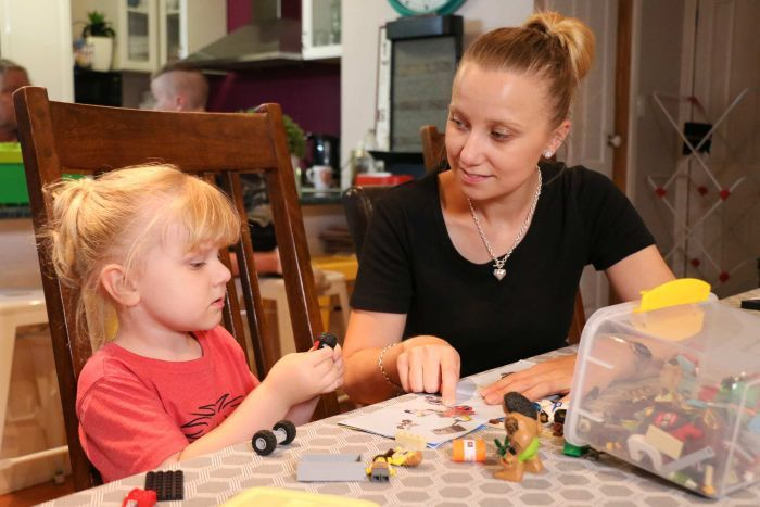 Cara and her son Ryland sit at a kitchen table playing with toys.
