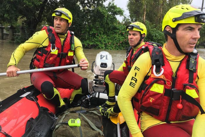 Three firefighters in lifejackets in an inflatable dinghy in floodwaters in Townsville.
