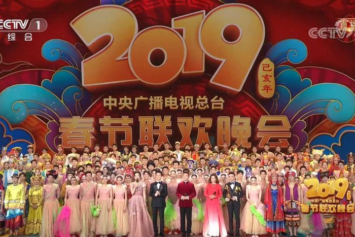 """Presenters and performers stand in front of a background saying """"2019 CCTV's Spring Festival Gala' sign."""
