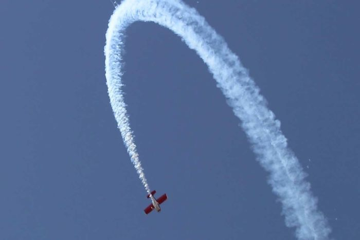 Plane in blue sky doing a loop with smoke tracing planes path
