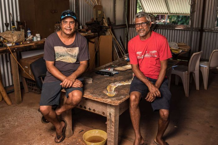 West Kimberley artists and brothers Garry and Darrell Sibosado sit on a low table in an art studio posing for a photo.