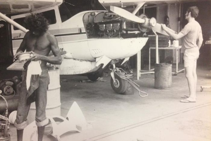A black and white picture of two men, one of them a young Yingiya Guyula, working at the MAF hangar.