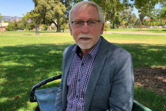 Geoff Harris sits on a park bench.