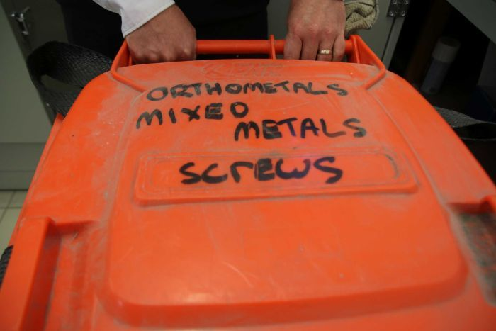 A large orange bin used to store metal screws to be recycled.