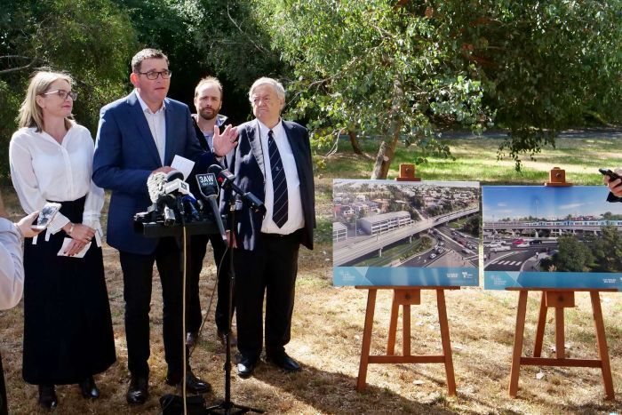 The Premier Daniel Andrews speaks into microphones near prints of artists impersonations of a elevated rail line.