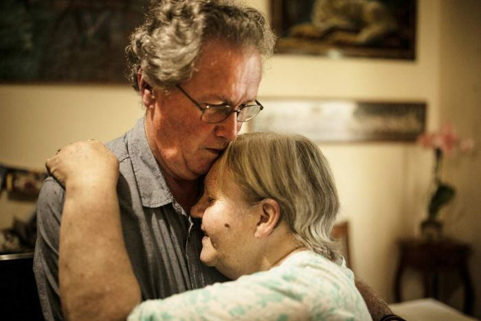 elderly couple hugging indoors