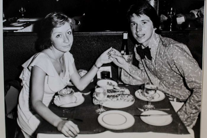 old black and white photograph of young couple at dining table holding hands