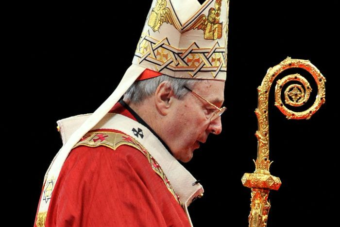 George Pell in full robes, holds a crook against a black background.