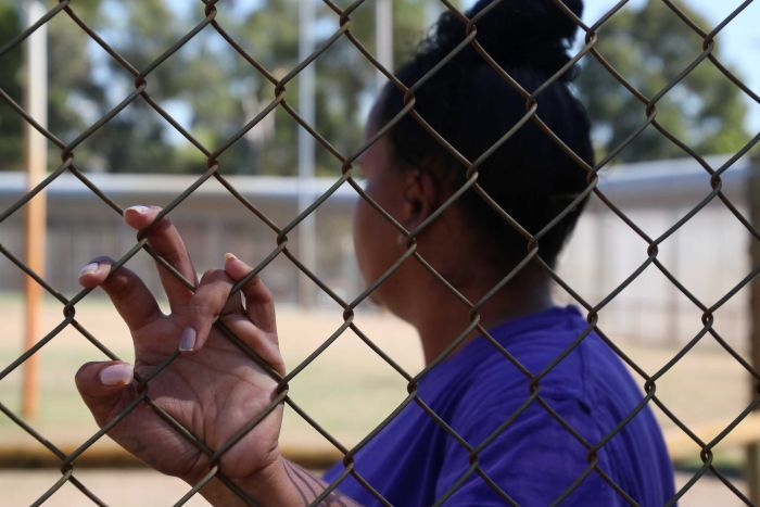 A prisoner looks into the distance as she has one hand on a prison fence.