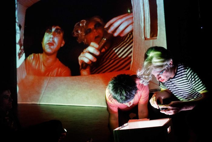 Stage shot, darkened, two men in front of stage stare into cardboard box while their faces are projected onto screen behind.