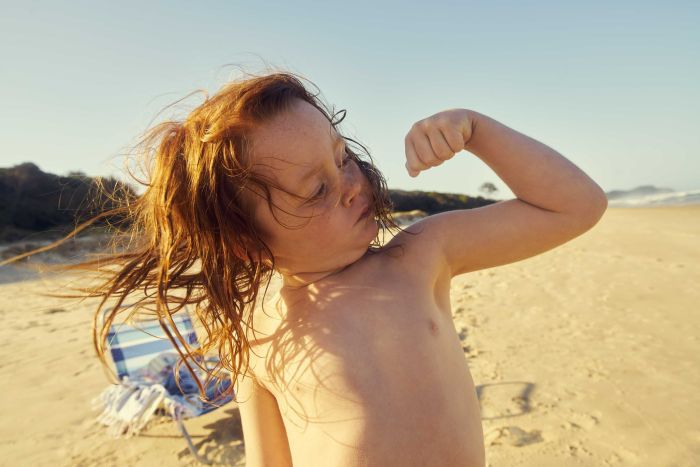 A child at the beach with shoulder-length hair flexes one arm's bicep while looking towards the muscle.