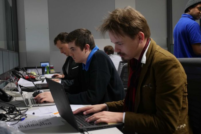 Three men working away at their computers.