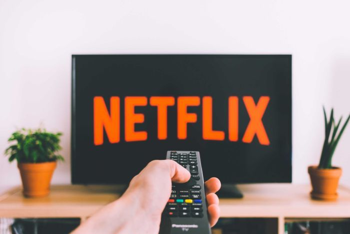 Person holding remote pointing at TV with Netflix