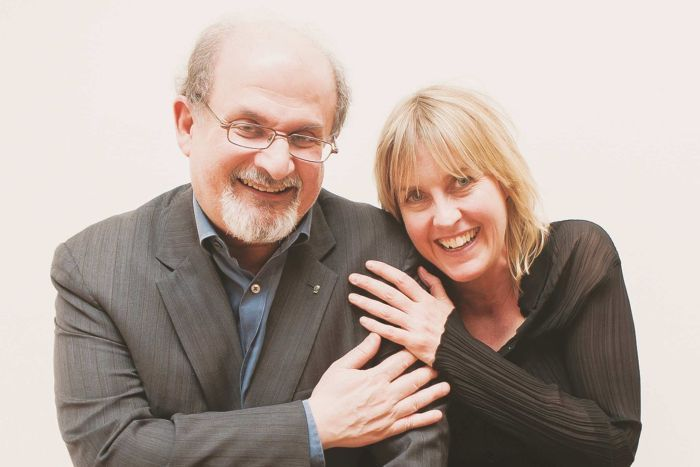 Salman Rushdie and Caro Llewellyn in a friendly pose with their hands on each others' shoulders.