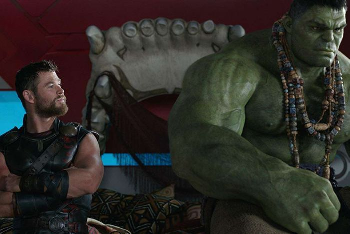 Thor and the Hulk sit on a giant bed made from a jaw.