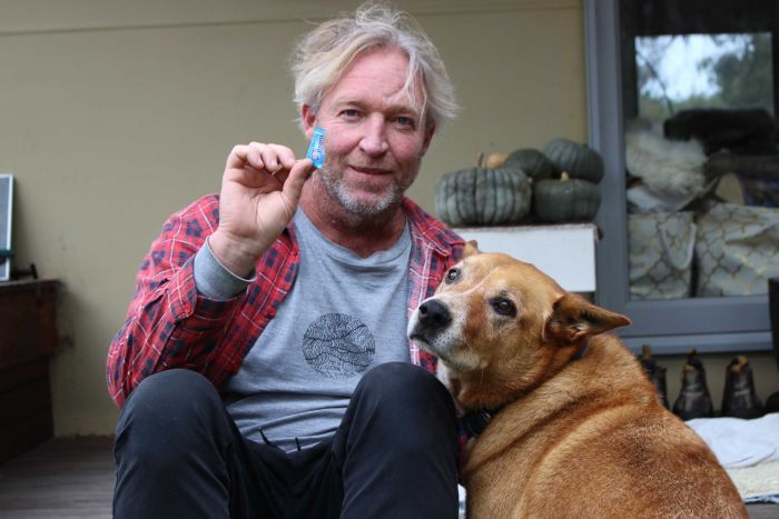 A middle-aged man sits on his verandah with his dog and holds a tiny piece of blue plastic.