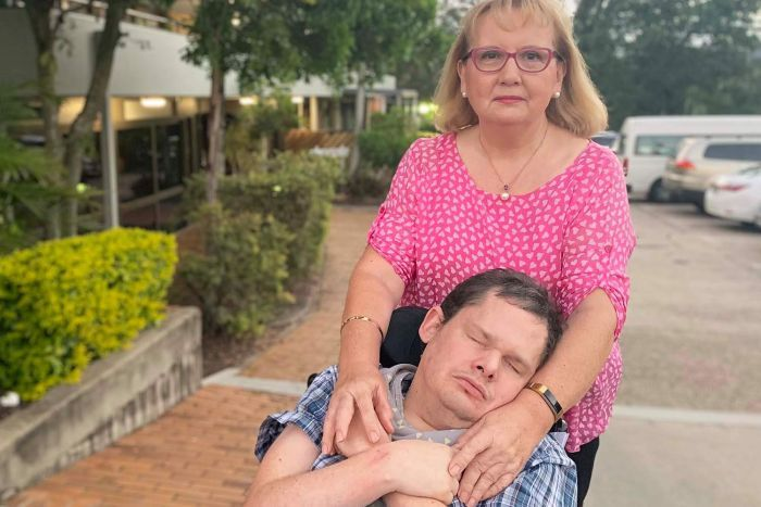 Patricia Dear stands with her arms hugging her son Kearon Dear, who is severely disabled, in Brisbane in April 2019.
