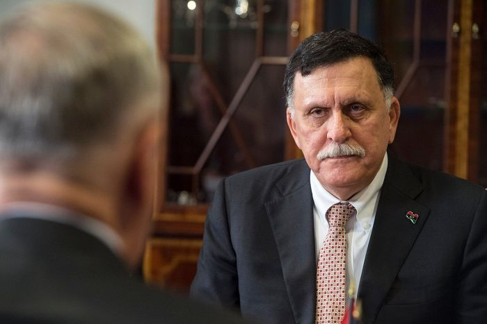 You look at Libya's Prime Minister Fayez Serraj in front of a brown cabinet from behind a man's shoulder who is blurred.