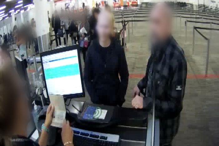 Two men stand at a customs desk at Perth Airport with their faces blurred as a customs officer checks a passport.