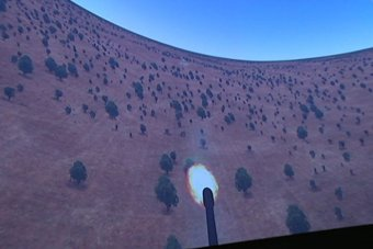 A video screen showing an animation with a missile firing from a plane down to a target on land