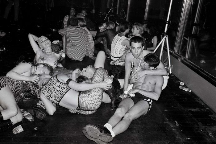 A black and white photo of a bunch of young queer people at a party in the early 90s