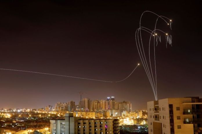 Rockets that leave a trail of light on a city.