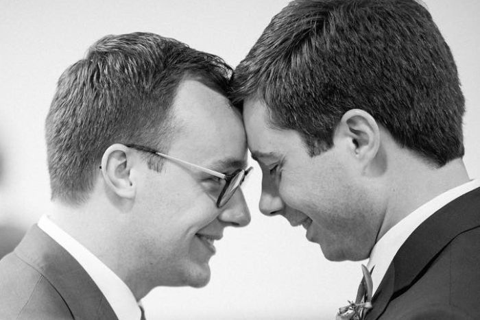 Two men in suits touch foreheads