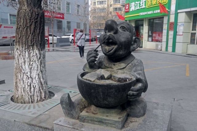 A statue of man eating from a bowl with chopsticks.